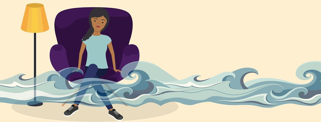Ocean waves rolling in front of a woman sitting in an armchair indoors.