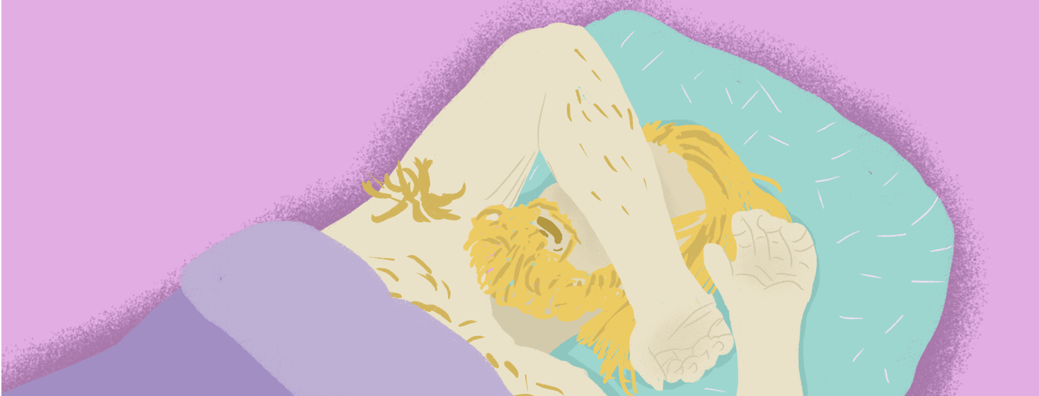 A blonde man with a beard is laying on a turquoise pillow under a purple blanket. He rests his arm on top of his face.