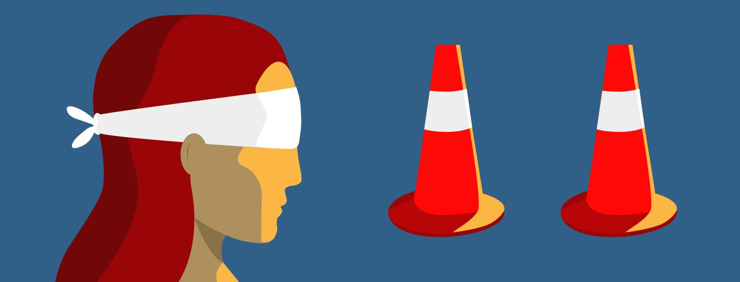 Blindfolded woman looking at traffic cones.