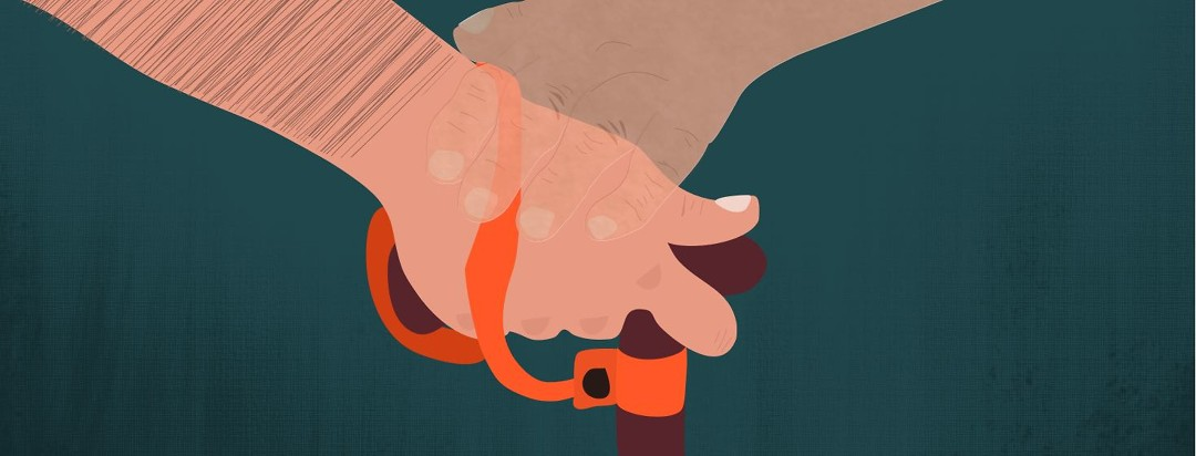 A hand holding the top of a cane with an orange cane strap wrapped around it. A shadow of an elderly relative's hand rests peacefully on top.
