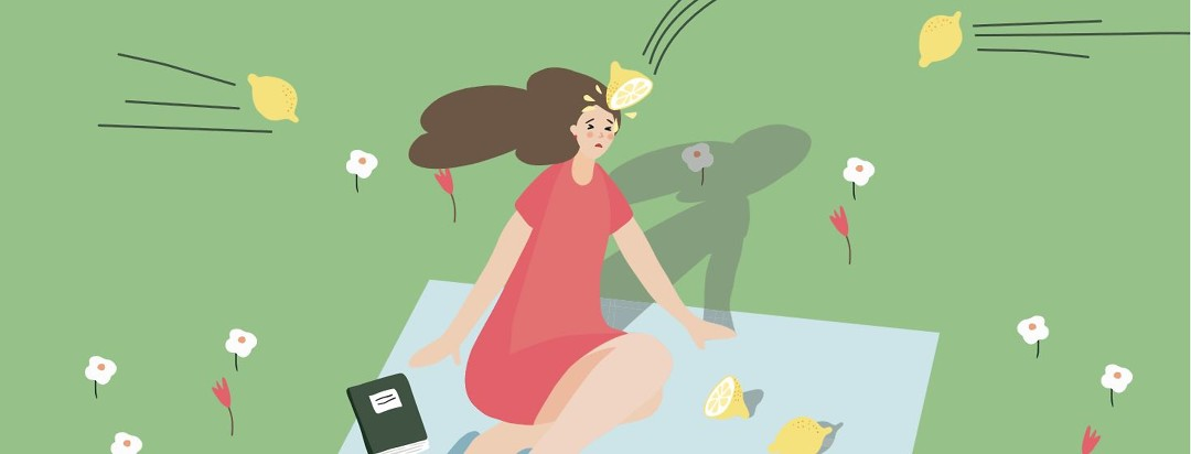 A woman sitting at a picnic and getting pelted with lemons. There is one that hits her in the head and drips down her face.