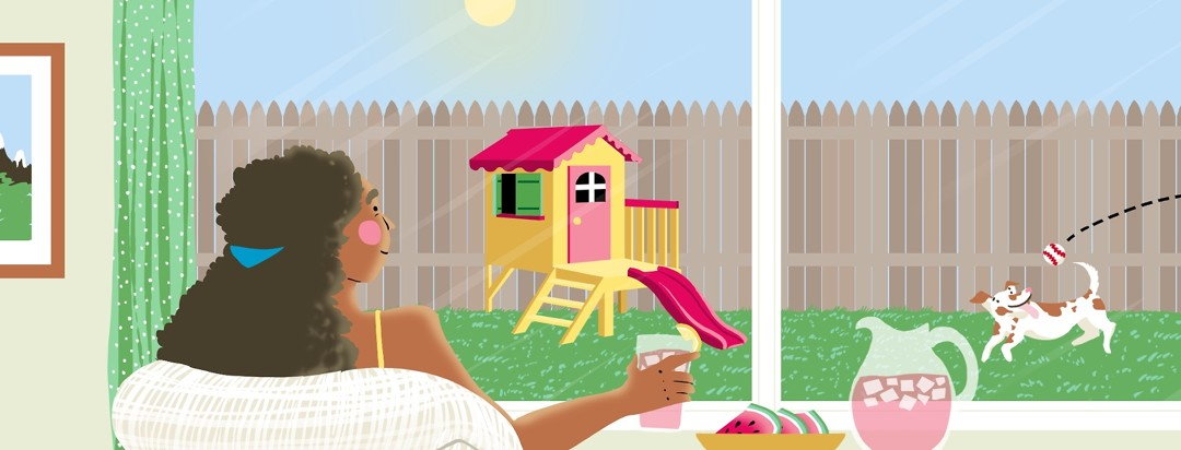 A woman with a cold drink in her hand and a plate of watermelon on a table next to her, smiles as she looks out the window at a sunny scene of a playhouse in her backyard and a dog running to catch a ball.