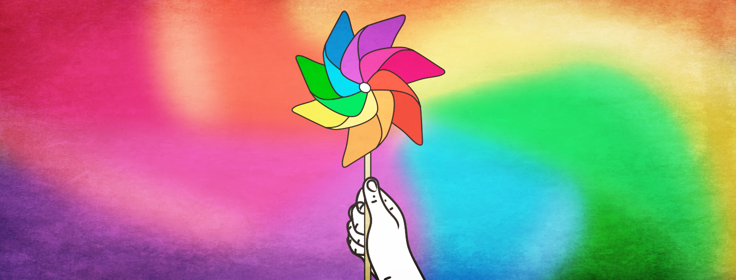 A hand holding a still pinwheel toy with a blurred mix of colors spinning in the background.