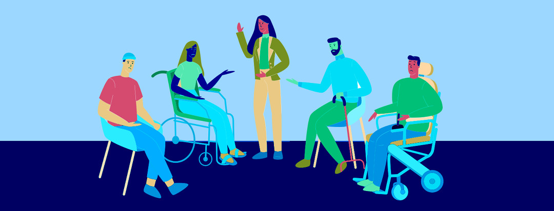 A group of differently abled people sitting and conversing together while one person standing in the middle gets the most attention.