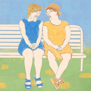 Two women laugh and talk on a park bench.