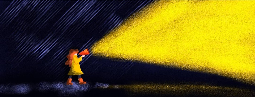A woman in a raincoat shines light in a dark rainstorm by speaking into a megaphone.