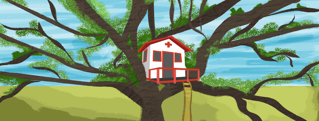 A children's treehouse is nestled in a large tree in a field. The house is decorated like a hospital.