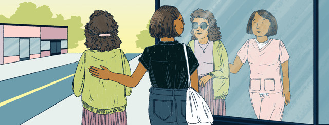 A younger woman walks with an older woman. The younger woman has her hand on the eldests woman's back, and looks into a store front's reflection to see herself in nursing attire.