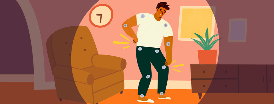 A man stands in the middle of a living room with his hands rubbing muscles. He has bolts for joints and is clutching his leg.