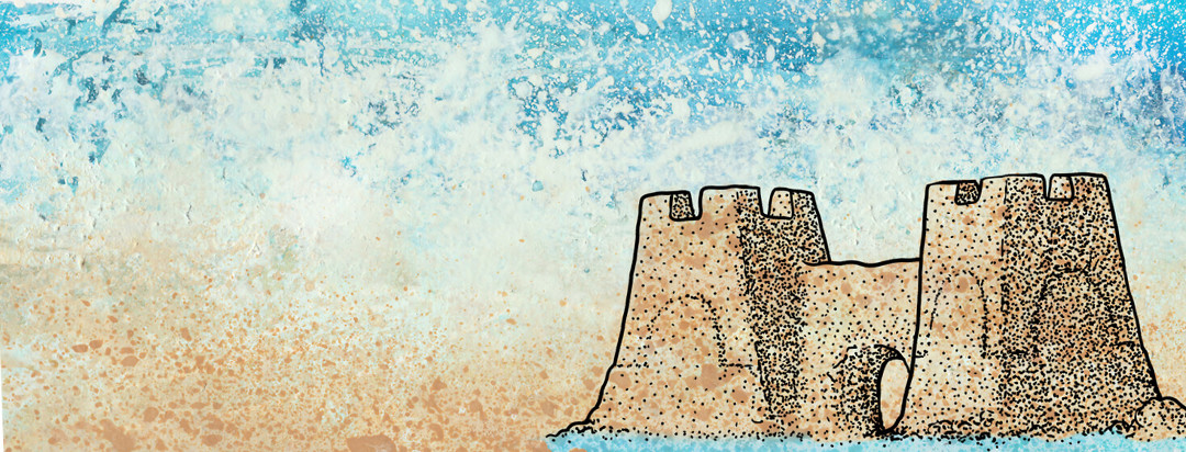 A sandcastle with a moat sits on the edge of the ocean. A large wave crashes in the background.