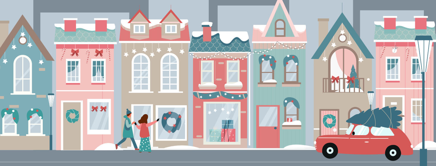 Shops are lined up along a busy street decorated for Christmas. Two girls are holding hands and pointing at a store window.
