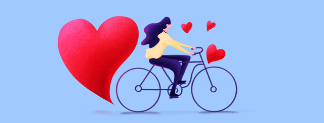 A woman is riding a bike with hearts flying up around her. There is a large heart coming off her back wheel.