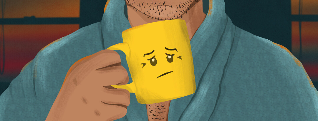 A man in a robe holds a yellow coffee mug with a tired lego face on it.
