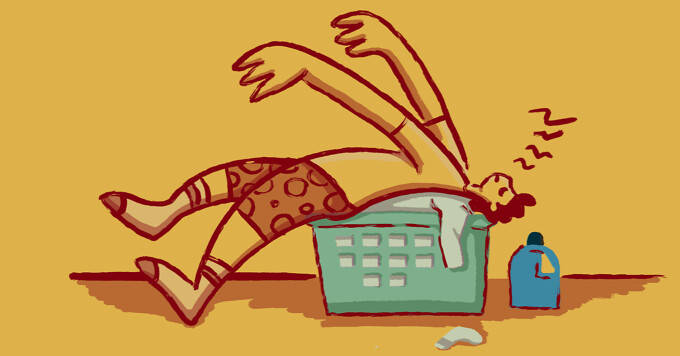 A man has fallen backwards into a full laundry basket of clothing and is taking a nap.