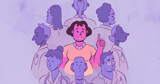 A woman stands in a circle of doctors who all have their backs turned to her.